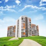 Edifici alti, colline verdi e strada contro il cielo Immagini Stock