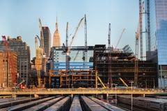 Edifici alti in costruzione e gru sotto un cielo blu a New York Immagine Stock