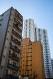 Edifici residenziali invecchiati vicino ad una nuova torre alta bianca Fotografia Stock Libera da Diritti