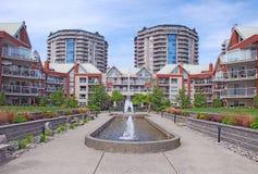 Edifici residenziali urbani moderni con la fontana sulla plaza nella parte anteriore sul fondo del cielo blu fotografia stock libera da diritti