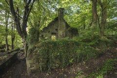 Edificio abandonado arruinado viejo fantasmagórico en paisaje grueso del bosque Fotos de archivo libres de regalías