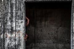edificio abandonado asustadizo con la mano del fantasma que sale de una puerta Imagenes de archivo