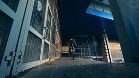 Edificio abandonado con un hombre joven que salta en su BMX metrajes