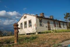 Edificio abandonado con una boca de incendios vieja en el primero plano Fotos de archivo libres de regalías