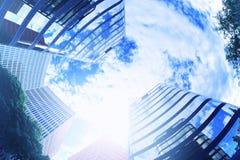 Edificio abstracto de la arquitectura con algunos rascacielos de debajo Llamarada del cielo y del sol de la nube espacio vacío de Imagen de archivo libre de regalías