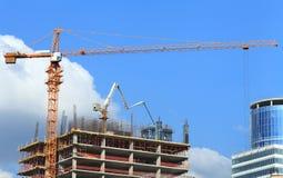 Edificio alto bajo construcción con la grúa y la bomba concreta Imagen de archivo
