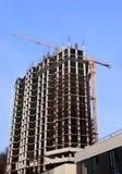 Edificio alto debajo de la construcción y de la grúa Fotografía de archivo libre de regalías