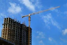 Edificio alto debajo de la construcción y de la grúa Foto de archivo