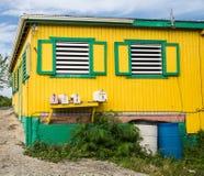 Edificio amarillo y verde viejo con los respiraderos de la ventana Imágenes de archivo libres de regalías