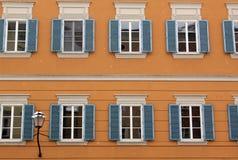 Edificio anaranjado con las ventanas abiertas azul Fotos de archivo libres de regalías