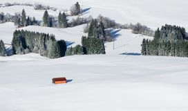Edificio anaranjado del granero en el paisaje blanco de la nieve Vista aérea del campo rural en día de invierno nevoso Weitnau, A Fotos de archivo libres de regalías