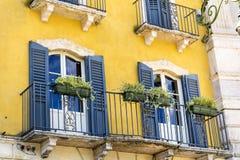 Edificio anaranjado típico con las ventanas antiguas en Verona Imagen de archivo libre de regalías