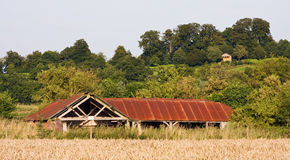Edificio arruinado con la azotea oxidada en un paisaje Foto de archivo