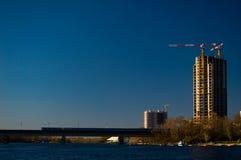 Edificio bajo construcción en un fondo azul con un puente del metro Foto de archivo libre de regalías