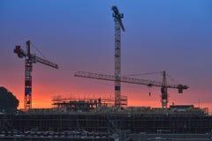 Edificio bajo construcción en la puesta del sol Escenas de la noche Imagen de archivo