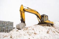 Edificio de apartamentos del invierno de la nieve del hoyo de arena del excavador Fotografía de archivo libre de regalías