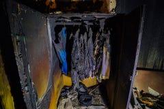 Edificio de apartamentos quemado interior Guardarropa quemado con ropa Imágenes de archivo libres de regalías