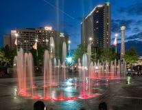 Edificio de CNN, parque olímpico centenario, y la fuente olímpica de los anillos enseguida después de la puesta del sol foto de archivo