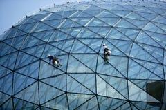 Edificio de cristal de la bóveda del espejo de la limpieza del escalador Foto de archivo libre de regalías