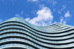 Edificio de cristal moderno contra el cielo nublado azul en fondo Foto de archivo