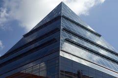 Edificio de cristal que refleja el cielo azul con las nubes blancas Foto de archivo