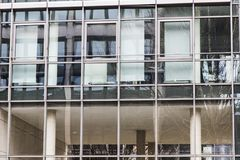 Edificio de la fachada con las ventanas en la luz del día con reflexiones Fotos de archivo libres de regalías