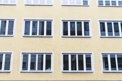Edificio de la fachada con las ventanas en la luz del día con reflexiones Imagen de archivo libre de regalías