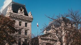 Edificio de la prefectura de la policía en París, Francia Vuelo francés de la bandera en cielo azul el día soleado Señal europea  almacen de metraje de vídeo