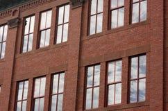 Edificio de ladrillo con las ventanas que reflejan las nubes y el cielo Imágenes de archivo libres de regalías