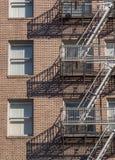 Edificio de ladrillo de gran altura con la escalera de la salida de incendios Fotos de archivo libres de regalías