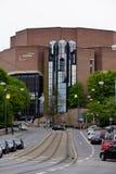 Edificio de ladrillo moderno con la calle y ferrocarril en frente fotografía de archivo