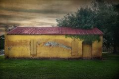 Edificio de ladrillo pintado amarillo con el tejado rojo aherrumbrado del metal fotografía de archivo libre de regalías