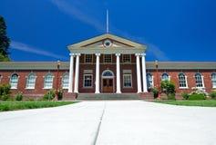 Edificio de ladrillo rojo clásico con la entrada blanca griega de la columna Foto de archivo