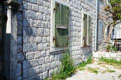 Edificio de ladrillo viejo con los obturadores Foto de archivo libre de regalías