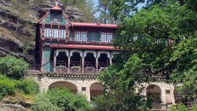Edificio de madera pintoresco en el acantilado, inclinación encima de la visión en día de primavera metrajes