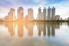 Edificio de oficinas con tono de la puesta del sol de la reflexión del agua foto de archivo libre de regalías