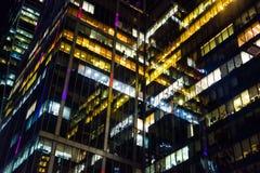 Edificio de oficinas moderno hecho del vidrio en la noche Luces en las ventanas de la oficina fotos de archivo