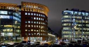 Edificio de oficinas y calle modernos con los coches en la noche Foto de archivo