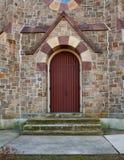 Edificio de piedra con la puerta roja Fotografía de archivo libre de regalías
