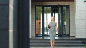 Edificio de salida de la mujer de negocios con el ordenador portátil Mujer rubia que sale de la oficina metrajes