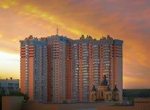 Edificio de varios pisos en la puesta del sol Foto de archivo libre de regalías