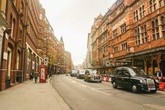 Edificio del vintage a lo largo del camino con el taxi negro en puesta del sol en Londres imagenes de archivo