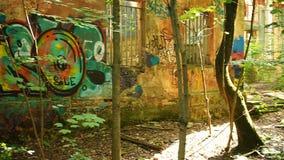 Edificio destruido en bosque con la pintada en las paredes metrajes