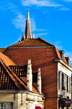 Edificio en Brujas con el chapitel de la iglesia Fotografía de archivo