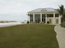 Edificio en la playa con un césped y una calzada imagen de archivo