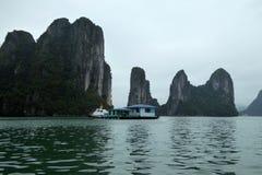 Edificio flotante rodeado por las islas dramáticas de la bahía larga Vietnam de la ha Imagen de archivo libre de regalías