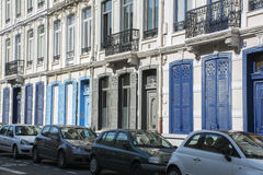 Edificio francés largo con los obturadores azules y la fila de coches Imagen de archivo