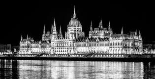 Edificio histórico iluminado del parlamento húngaro en el terraplén del río Danubio en Budapest por noche imágenes de archivo libres de regalías