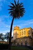 Edificio histórico y palmeras en la puesta del sol en Palermo, Sicilia Imagen de archivo