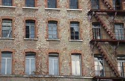 edificio industrial dilapidado con la salida de incendios oxidada con rojo Foto de archivo